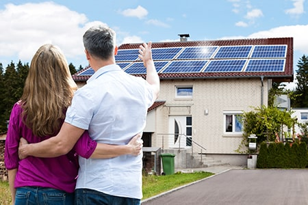 Couple Standing in Front of House Looking at Solar Panels on Roof